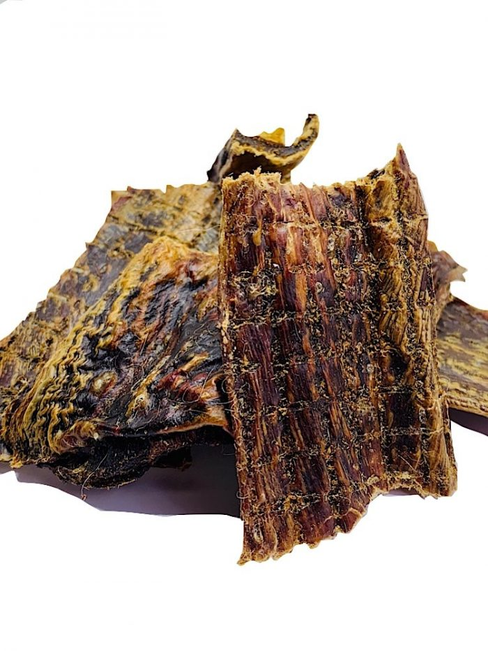 Photograph of 5 or 6 dried pieces of kangaroo jerky in a pile on a white background