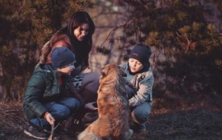 two boys with their mum and the family dog happily crouching in a wooded area