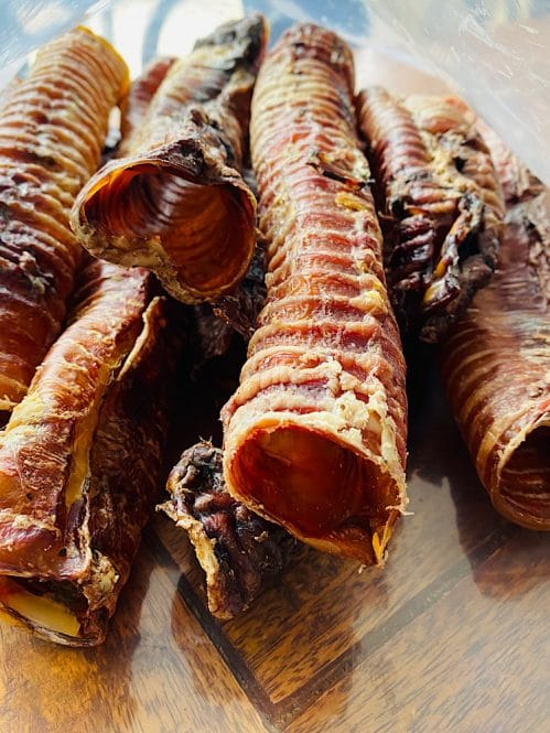 Photograph of seven Drool Pet Co. dehydrated beef trachea stacked on top another.