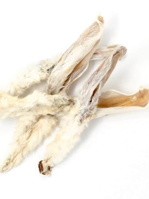 Photograph of a Drool Pet Co. naturally dehydrated rabbit ears with fur on a white background.