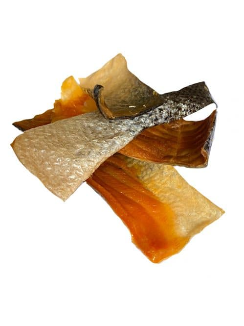 Photograph of a Drool Pet Co. dried salmon strips on a white background.